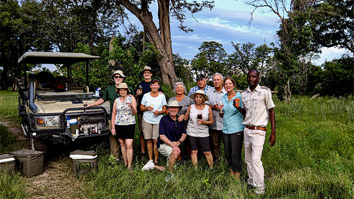 A Lion World Travel group celebrates after a tour in Serengeti